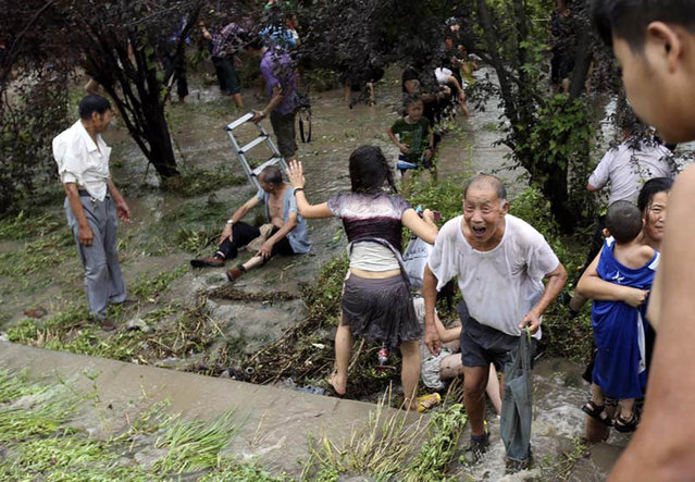 Spectators get to their feet, after being swept down a hill by huge waves while watching tides of Qiantang River on August 22, 2013 in Haining, China. (Photo by ChinaFotoPress via The Atlantic)
