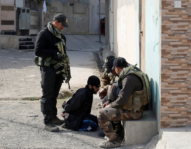 Members of an  Iraqi Special forces intelligence team talk to suspected Islamic State fighter in Mosul, Iraq November 27, 2016. (Photo by Goran Tomasevic/Reuters)