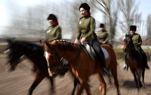 """Women riders wearing Cossacks uniforms take part in a parade before the horseback riding equestrian sport tournament """"Victory Cup Stage"""" in Bishkek, Kyrgyzstan on April 4, 2021. (Photo by Vyacheslav Oseledko/AFP Photo)"""