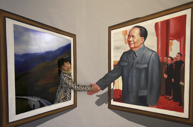 A girl poses for a photograph next to a 3D painting of Chairman Mao Zedong at an exhibition in Binzhou, Shandong province, December 15, 2013. (Photo by Reuters/Stringer)