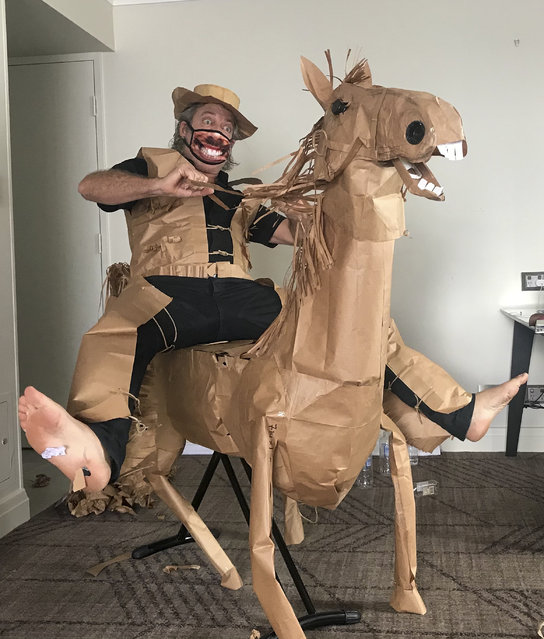 David Marriott poses with his paper horse in his hotel room in Brisbane, Australia, April 1, 2021. While in quarantine inside his Brisbane hotel room, art director Russell Brown was bored and started making a cowboy outfit from the paper bags his meals were being delivered in. His project expanded to include a horse and a clingfilm villain that he has daily adventures with, in images that have gained a huge online following. (Photo by David Marriott via AP Photo)