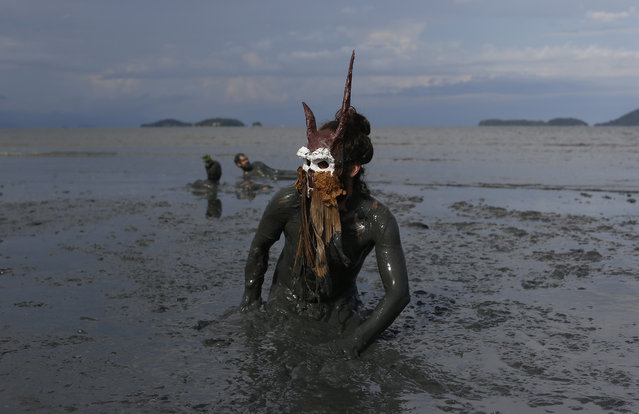 "A reveler wearing a costume plays in the mud during the traditional ""Bloco da Lama"" or ""Mud Block"" carnival party, in Paraty, Brazil, Saturday, February 14, 2015. (Photo by Leo Correa/AP Photo)"