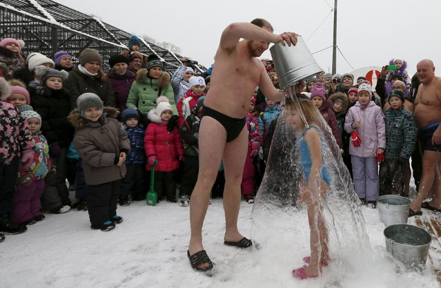 Visitors watch as Grigory Broverman, a member of the Cryophile winter swimmers club, pours a bucket of cold water over his 6-year-old daughter Liza during a flash mob, part of a celebration of Polar Bear Day at the Royev Ruchey Zoo in a suburb of the Siberian city of Krasnoyarsk, Russia, November 29, 2015. The air temperature was around minus 5 degrees Celsius. (Photo by Ilya Naymushin/Reuters)