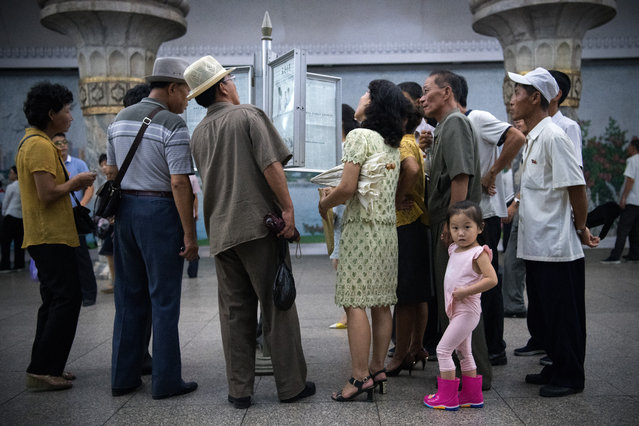 A little girl looks back away as people read a newspaper displayed in a station on the Pyongyang metro on August 21, 2018 in Pyongyang, North Korea. (Photo by Carl Court/Getty Images)
