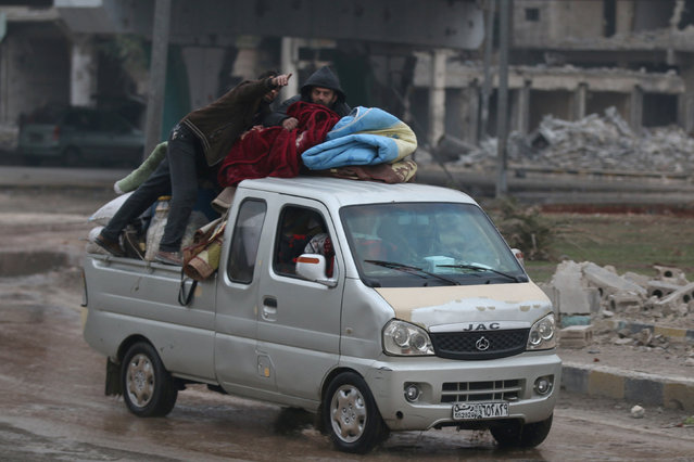 People ride on a pick-up truck as they flee deeper into the remaining rebel-held areas of Aleppo, Syria December 7, 2016. (Photo by Abdalrhman Ismail/Reuters)