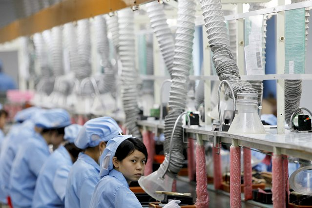 An employee looks up while working along a production line in Suzhou Etron Electronics Co. Ltd's factory in Suzhou, Jiangsu province in this June 8, 2010 file photo. (Photo by Aly Song/Reuters)