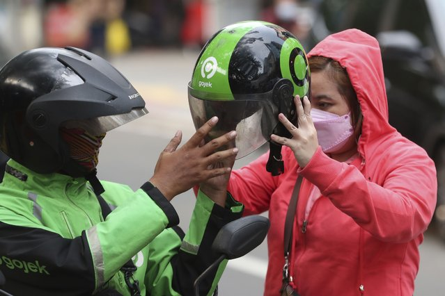 A Gojek driver gives a helmets to a customer in Jakarta, Indonesia, Monday, May 17, 2021. Indonesian ride hailing company Gojek and e-commerce firm Tokopedia said Monday that they are merging, in the largest ever deal in the country's history. (Photo by Achmad Ibrahim/AP Photo)
