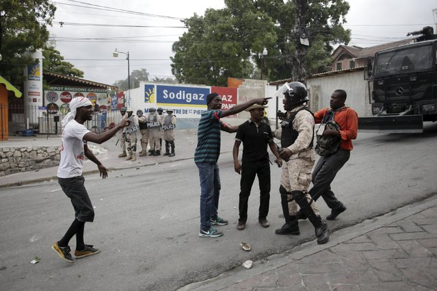 Protesters argue with a National Police officer during a demonstration against the electoral process in Port-au-Prince, Haiti, January 22, 2016. Haiti postponed a U.S.-backed presidential election as violent protests erupted on Friday after the opposition candidate vowed to boycott the vote over alleged fraud. (Photo by Andres Martinez Casares/Reuters)