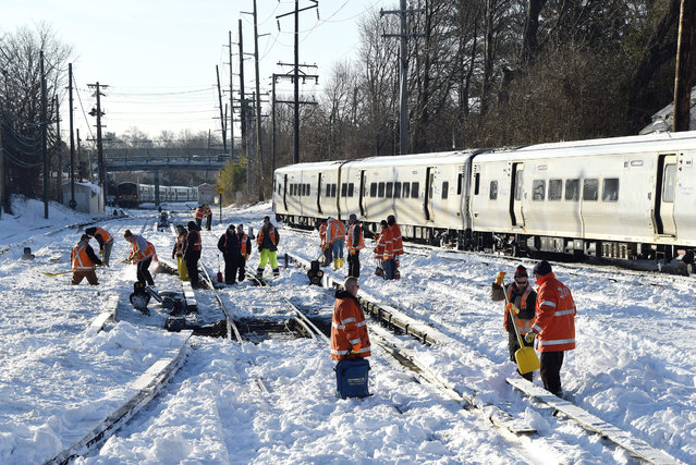Workers clear the tracks of snow at the Port Washington branch of the Long Island Railroad, Monday, January 25, 2016, in Port Washington, N.Y.. Service is suspended on the Port Washington branch due to the recent snow storm. (Photo by Kathy Kmonicek/AP Photo)