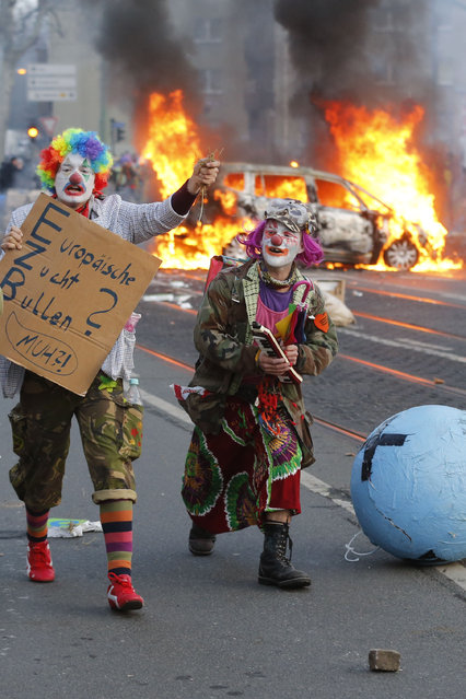 Two demonstrators dressed as clowns walk past a burning car as activists try to blockade the new headquarters of the ECB to protest against government austerity and capitalism Wednesday morning, March 18, 2015 in Frankfurt, Germany. (Photo by Michael Probst/AP Photo)