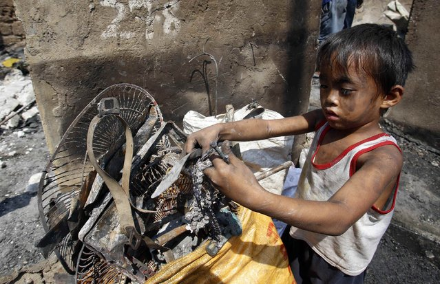 A boy collects recyclable materials recovered from a fire at a residential district in Malabon, Metro Manila March 18, 2015. Two people were killed and 500 families rendered homeless in Malabon on Tuesday after a fire caused by an electrical short circuit in the area broke out, according to local media reports. (Photo by Erik De Castro/Reuters)