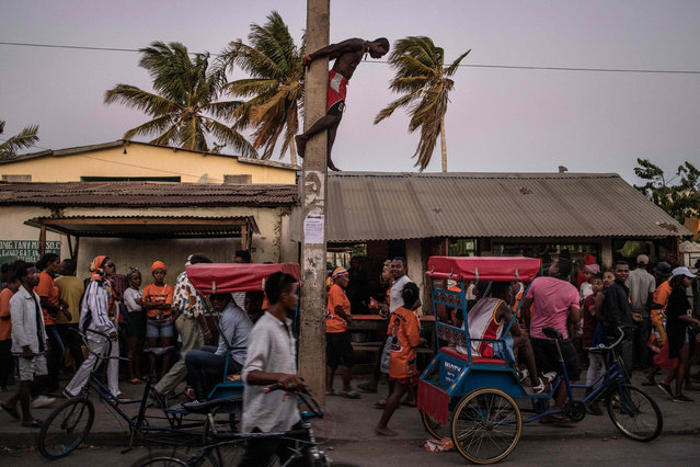 A man dangles from an electricity pole as he watches supporters of Madagascar presidential candidate Andry Rajoelina, streaming towards a rally in Tulear, on November 4, 2018. Former President Marc Ravalomanana and rival Andry Rajoelina are frontrunners in the November 7 ballot in Madagascar, where protests earlier this year erupted over a government attempt to reform electoral rules. After months of tension, the Constitutional Court ordered a caretaker government to organise the ballot. If none of the candidates gets more than 50 percent of the votes cast, a second round will be held on December 19. (Photo by Marco Longari/AFP Photo)