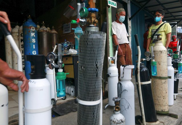 People wearing protective face masks stand with their oxygen cylinders outside a store to get them refilled, amid the coronavirus disease (COVID-19) outbreak in Jakarta, Indonesia, June 28, 2021. (Photo by Ajeng Dinar Ulfiana/Reuters)