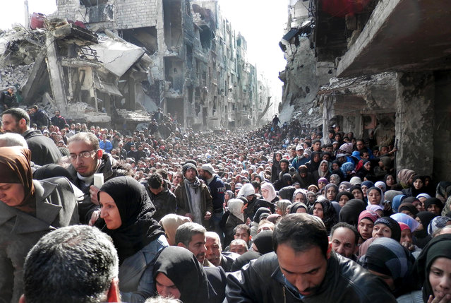 In this January 31, 2014 file photo released by the United Nations Relief and Works Agency for Palestine Refugees in the Near East (UNRWA), shows residents of the besieged Palestinian camp of Yarmouk, queuing to receive food supplies, in Damascus, Syria. That year, the U.N. was able to deliver food to about five percent of people in besieged areas including Yarmouk, while today estimates show the organization is reaching less than one percent. (Photo by UNRWA via AP Photo)