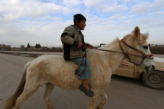 A boy rides a horse along a street at the Syrian town of Ras al-Ain, close to the Turkish border, January 23, 2016. (Photo by Rodi Said/Reuters)