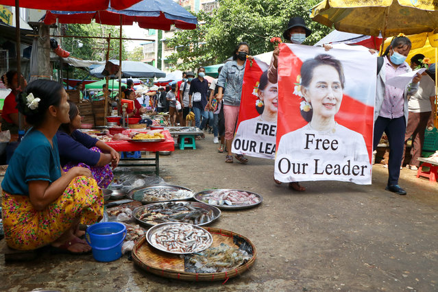 Anti-coup protesters walk through a market with images of ousted Myanmar leader Aung San Suu Kyi at Kamayut township in Yangon, Myanmar Thursday, April 8, 2021. They walked through the markets and streets of Kamayut township with slogans to show their disaffection for military coup. (Photo by AP Photo/Stringer)