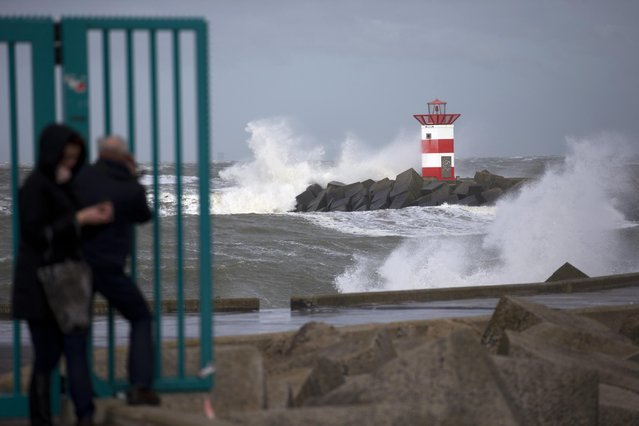 People take pictures of the waves ceasing into a storm barrier and a lighthouse during stormy weather at the entrance to the port of Scheveningen, near The Hague, Netherlands, Tuesday, March 31, 2015. A storm with wind speeds of up to 110 kilometers (68 miles) per hour passed over The Netherlands and Germany. (Photo by Peter Dejong/AP Photo)