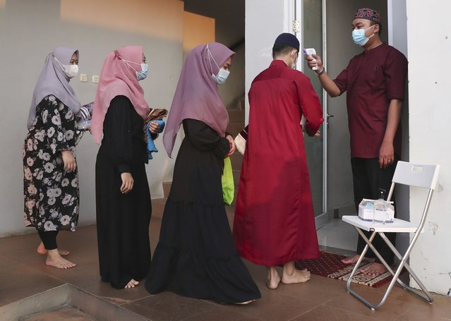 An official takes the body temperature reading of worshippers arriving for an Eid al-Adha prayer as to curb the spread of coronavirus during an Eid al-Adha prayer at Zona Madina mosque in Bogor, Indonesia,Tuesday, July 20, 2021. Muslims across Indonesia marked a grim Eid al-Adha festival for a second year Tuesday as the country struggles to cope with a devastating new wave of coronavirus cases and the government has banned large gatherings and toughened travel restrictions. (Photo by Tatan Syuflana/AP Photo)