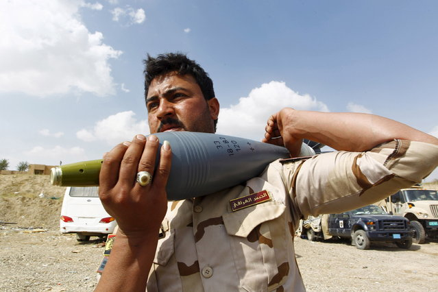 A member of the Iraqi army carry a rocket as he prepares to launch towards Islamic State militants in Tikrit, March 30, 2015. (Photo by Alaa Al-Marjani/Reuters)