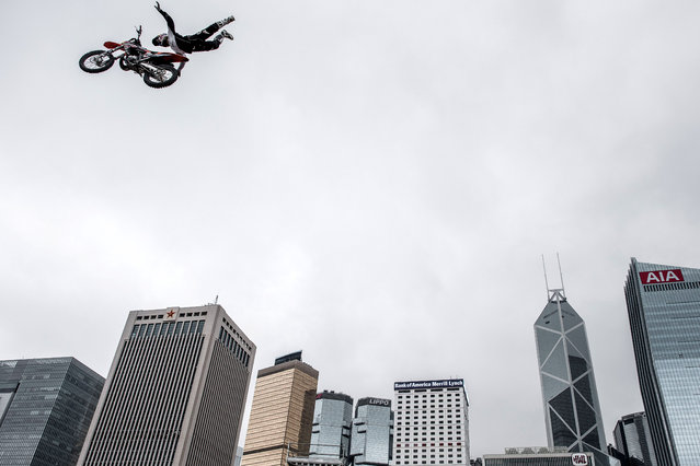 A motocross pilot performs a stunt jump in front of the city's skyline during a promotional event for an energy drink in Hong Kong on April 3, 2015. The famous city's skyline is often used as part of the promotional events by various brands and organisations. (Photo by Philippe Lopez/AFP Photo)