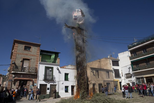 A figure representing Judas burns on top of a cross in Tielmes, Spain on Easter Sunday  Sunday, April 5, 2015 marking the end of Holy week. Youths from the village who have recently turned 18 drag a tree trunk from a forest and erect it in the square with the help of older men before it's burned. The burning, originally a pagan ritual, is a cleansing ceremony to rid  bad things that have happened during the year. (Photo by Paul White/AP Photo)