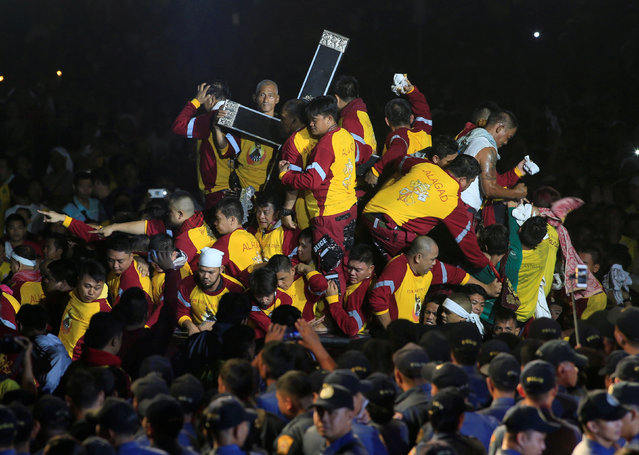 Devotees climb on a carriage to hold the Black Nazarene during an annual procession in Rizal park, metro Manila, Philippines January 9, 2017. (Photo by Romeo Ranoco/Reuters)