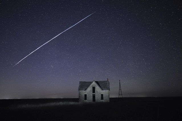 File-In this photo taken May 6, 2021, with a long exposure, a string of SpaceX StarLink satellites passes over an old stone house near Florence, Kan. The train of lights was actually a series of relatively low-flying satellites launched by Elon Musk's SpaceX as part of its Starlink internet service earlier this week. (Photo by Reed Hoffmann/AP Photo/File)