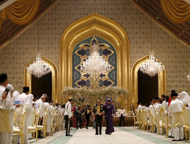 Brunei's newly wed royal couple, Prince Abdul Malik and Dayangku Raabi'atul 'Adawiyyah Pengiran Haji Bolkiah, leave the royal wedding banquet at the Nurul Iman Palace in Bandar Seri Begawan April 12, 2015. (Photo by Olivia Harris/Reuters)