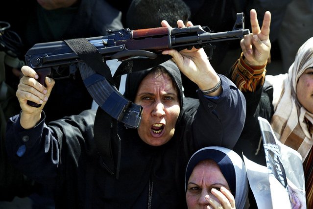 A Palestinian woman holds an AK-47 above her head as she shouts pro-Arafat slogans during a rally to mark the 39th anniversary of the Palestinian National Liberation Movement's (Fatah) foundation on December 31, 2003 in Gaza City, Gaza Strip. (Photo by Abid Katib/Getty Images)