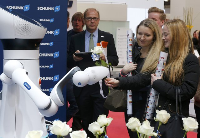 A robotic arm presents flowers to girls at the booth of Schunk at the world's largest industrial technology fair, the Hannover Messe, in Hanover April 13, 2015. (Photo by Wolfgang Rattay/Reuters)