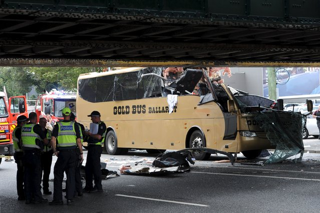 Emergency workers stand alongside a bus which crashed into an overhead barrier protecting a low bridge in South Melbourne, Australia February 22, 2016. (Photo by Mal Fairclough/Reuters/AAP)