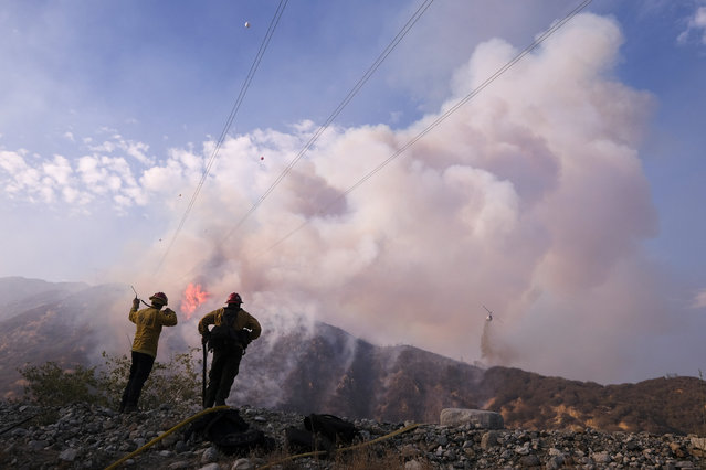 Firefighters watch as a helicopter drops water at the South Fire burning in Lytle Creek, San Bernardino County, north of Rialto, Calif., Wednesday, August 25, 2021. (Photo by Ringo H.W. Chiu/AP Photo)