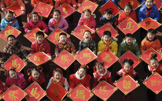 "Children pose for pictures with their paper-cut works of the Chinese character ""horse"", ahead of the Year of the Horse in Chinese zodiac, at a primary school in Jiujiang, Jiangxi province, December 31, 2013. (Photo by Reuters/China Daily)"