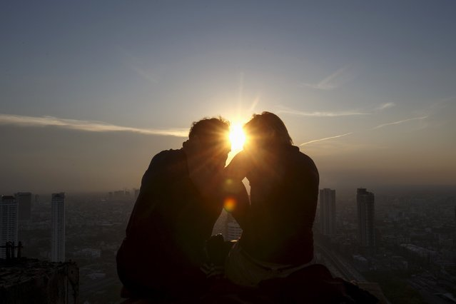 A couple enjoy the sunset on the roof top of an abandoned building in Bangkok April 19, 2015. (Photo by Athit Perawongmetha/Reuters)