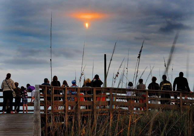 A SpaceX Falcon 9 Rocket with a commercial satellite aboard lights up the sky during a successful launch from the Cape Canaveral Air Force Station as people line the boardwalk, Monday, January 6, 2014, along the seashore in Cape Canaveral, Fla. (Photo by Craig Rubadoux/AP Photo/Florida Today)