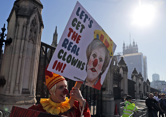A Demonstrator protests at the entrance of the Houses of Parliament in London, Tuesday, Febryary 26, 2019. Bank of England Governor Mark Carney has warned that the Brexit uncertainty that has dogged the British economy over the past couple of years will remain even if lawmakers agree to a withdrawal agreement with the European Union in coming weeks. (Photo by Frank Augstein/AP Photo)