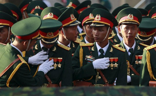 Vietnamese soldiers adjust medals for their comrades during a rehearsal for a military parade as part of the 40th anniversary of the fall of Saigon in southern Ho Chi Minh City (formerly Saigon City), Vietnam, on April 26, 2015. Vietnam marks the 40th anniversary of the fall of Saigon on April 30, the event that ended a war that lasted over 30 years, killing up to four million Vietnamese. (Photo by Reuters/Kham)