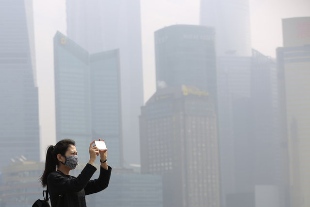 A woman wears a mask as she takes pictures on the Bund on a hazy day in Shanghai, China, March 7, 2016. (Photo by Aly Song/Reuters)