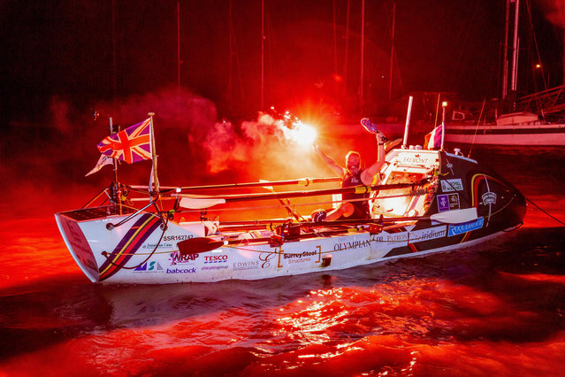 "Lee Spencer, a 49-year-old former British marine, known as ""The Rowing Marine"", holds a red flare and his prosthesis as he arrives in Cayenne, French Guiana, early on March 11, 2019, after smashing solo Atlantic rowing record from mainland Europe to South America. - Spencer originally embarked in Portimao, Portugal. He spent 60 days offshore to cross the Atlantic through 3,800 nautical miles, becoming the first physically disabled person to make the solo crossing from mainland Europe to South America and also smashing the able-bodied record, according to his team. (Photo by Jody Amiet/AFP Photo)"