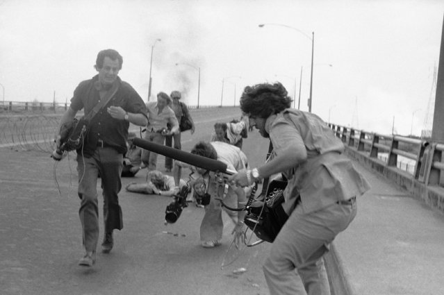 Unidentified members of a television news crew run for cover in Saigon on Monday, April 28, 1975 during fighting between South Vietnamese Government troops and Communist forces on the northern outskirts of Saigon. (Photo by Thauh Nuy/AP Photo)