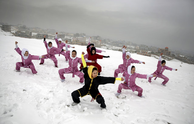 Shaolin martial arts students follow their trainer, Sima Azimi, 20, in black, during a training session on a hilltop in Kabul, Afghanistan, Tuesday, January 25, 2017. Sima Azimi, 20, who is originally from Jaghuri in central Afghanistan, trains nine students in the martial arts to prepare for Olympic competitions, but also to protect themselves on the streets of Kabul, where women are routinely harassed. (Photo by Massoud Hossaini/AP Photos)