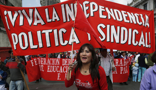 "A woman walks in front of a banner with a message that reads in Spanish; ""Long live political independence and unions"", in a May Day march, in La Paz, Bolivia, Friday, May 1, 2015. (Photo by Juan Karita/AP Photo)"