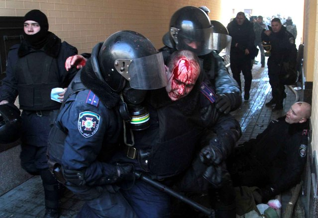 Policeman evacuate a wounded colleague during clashes with anti-government protesters in Kiev, on February 18, 2014. (Photo by Sergey Starostenko/Newscom/SIPA Press)