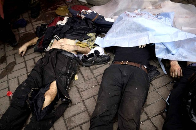 Dead bodies lay covered on the ground during clashes with riot police in central Kiev on February 20, 2014 in Kiev. At least 25 protesters were killed on February 20 in fresh clashes between thousands of demonstrators and heavily-armed riot police in the heart of Kiev, AFP correspondents at the scene said. The bodies of eight demonstrators were lying outside Kiev's main post office on Independence Square, an AFP reporter said. (Photo by Bulent Kilic/AFP Photo)