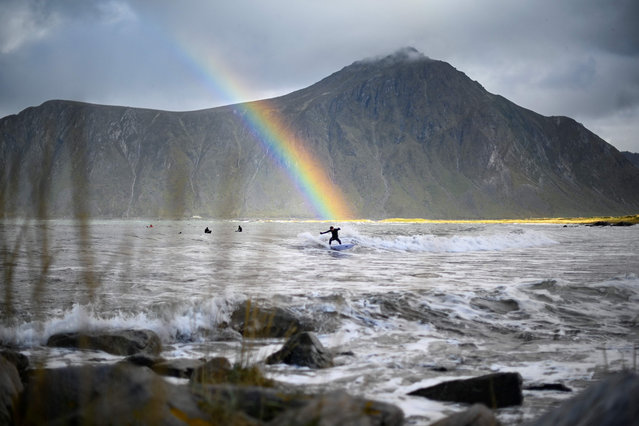 Surfer Anker Olsen Frantzen, 17, of Norway, rides a wave under a rainbow during a free surf session on September 26, 2018, in Flakstad, northern Norway, at the eve of the Lofoten Masters 2018. Lofoten Masters 2018, the most northern Surf contest, will be held from September 27 to 30, in Unstad, within Arctic circle. (Photo by Olivier Morin/AFP Photo)