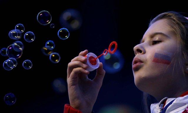 A girl with a Russian flag painted on her face blows bubbles as she waits for the start of the closing ceremony. (Photo by Gregorio Borgia/Associated Press)