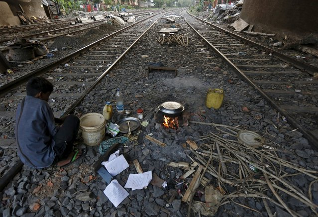 Ratan Samanta, 29, cooks a meal between the railway tracks in a slum area of Kolkata, India, March 13, 2016. (Photo by Rupak De Chowdhuri/Reuters)