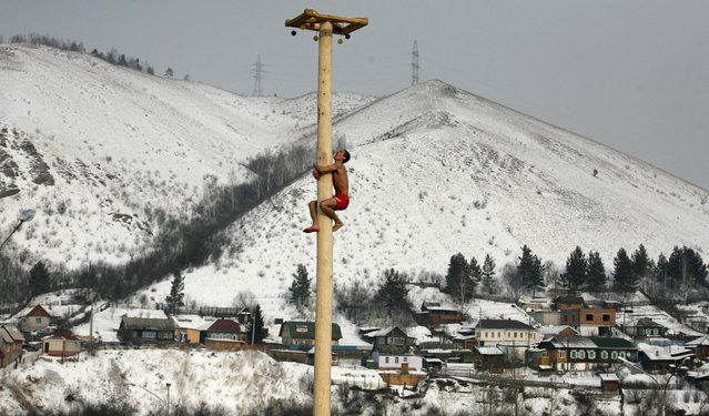 A man climbs up a smooth wooden column to win a contest during the celebrations of Maslenitsa, or Pancake Week, at the Bobrovy Log ski resort in the suburbs of Russia's Siberian city of Krasnoyarsk, March 2, 2014. Maslenitsa is widely viewed as a pagan holiday marking the end of winter and is celebrated with pancake eating, while the Orthodox Church considers it as the week of feasting before Lent. (Photo by Ilya Naymushin/Reuters)