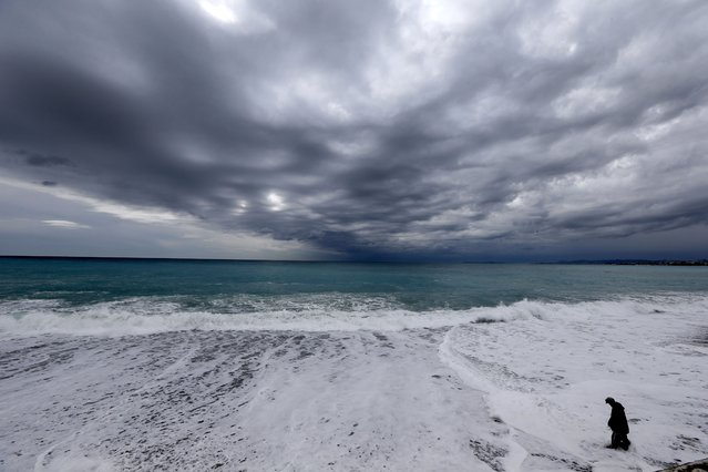 A man walks into the water as waves crash onto the shore of the Mediterranean sea in Nice, France on February 28, 2016. (Photo by Valery Hache/AFP Photo)