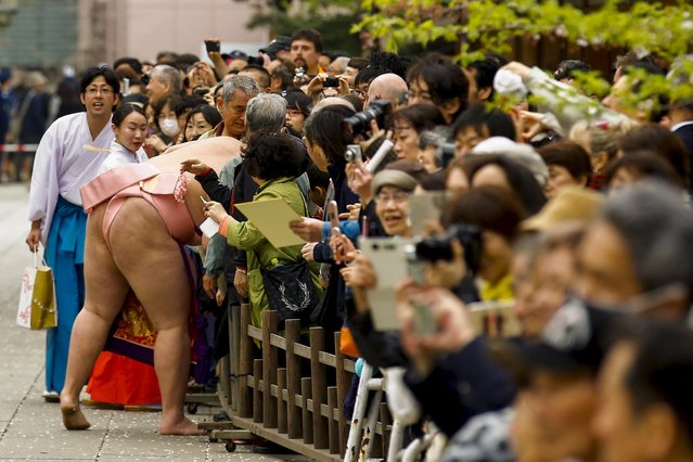 "A sumo wrestler greets supporters before the start of the ""Honozumo"" ceremonial sumo tournament at the Yasukuni Shrine in Tokyo April 3, 2015. (Photo by Thomas Peter/Reuters)"